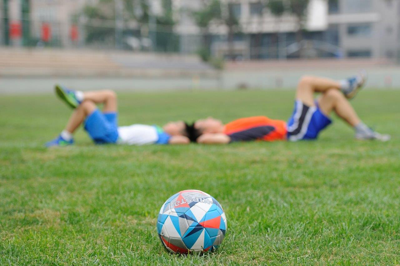 kids laying down in a soccer field