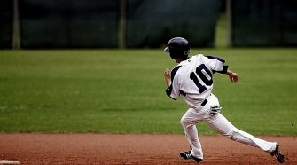Young Baseball Athlete in Uniform Running for Home Base
