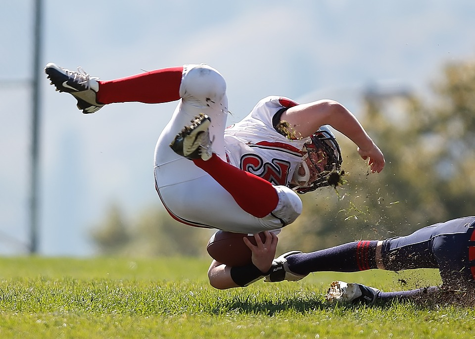 Young Football Athlete Falling on Grass