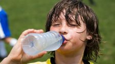 Young soccer athlete sweating and drinking water