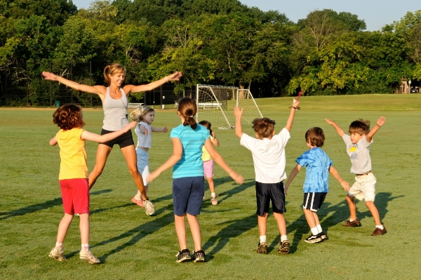 Instructor and children doing high-intensity interval training