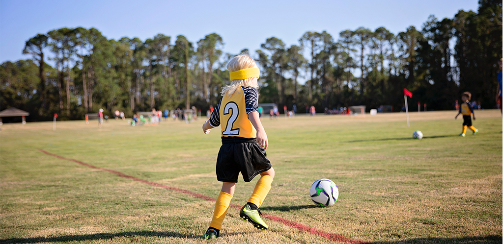 boy playing soccer in green soccer cleats
