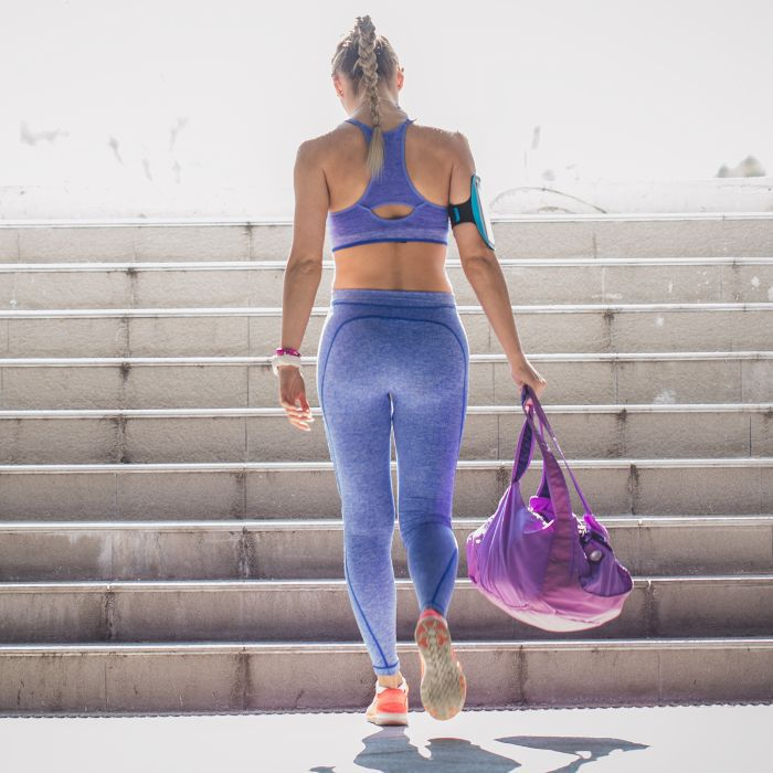 girl walking up the stairs with gym bag