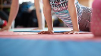Children doing yoga poses on rubber mat