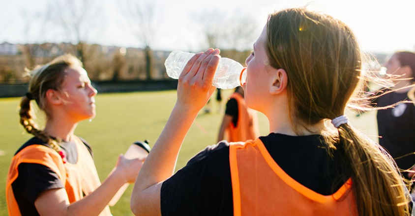 Girl drinking water on sidelines