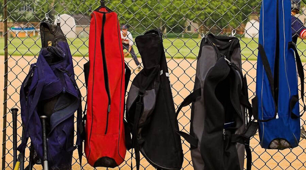 A view of multi-colored sports bags hanging up to dry on fencing