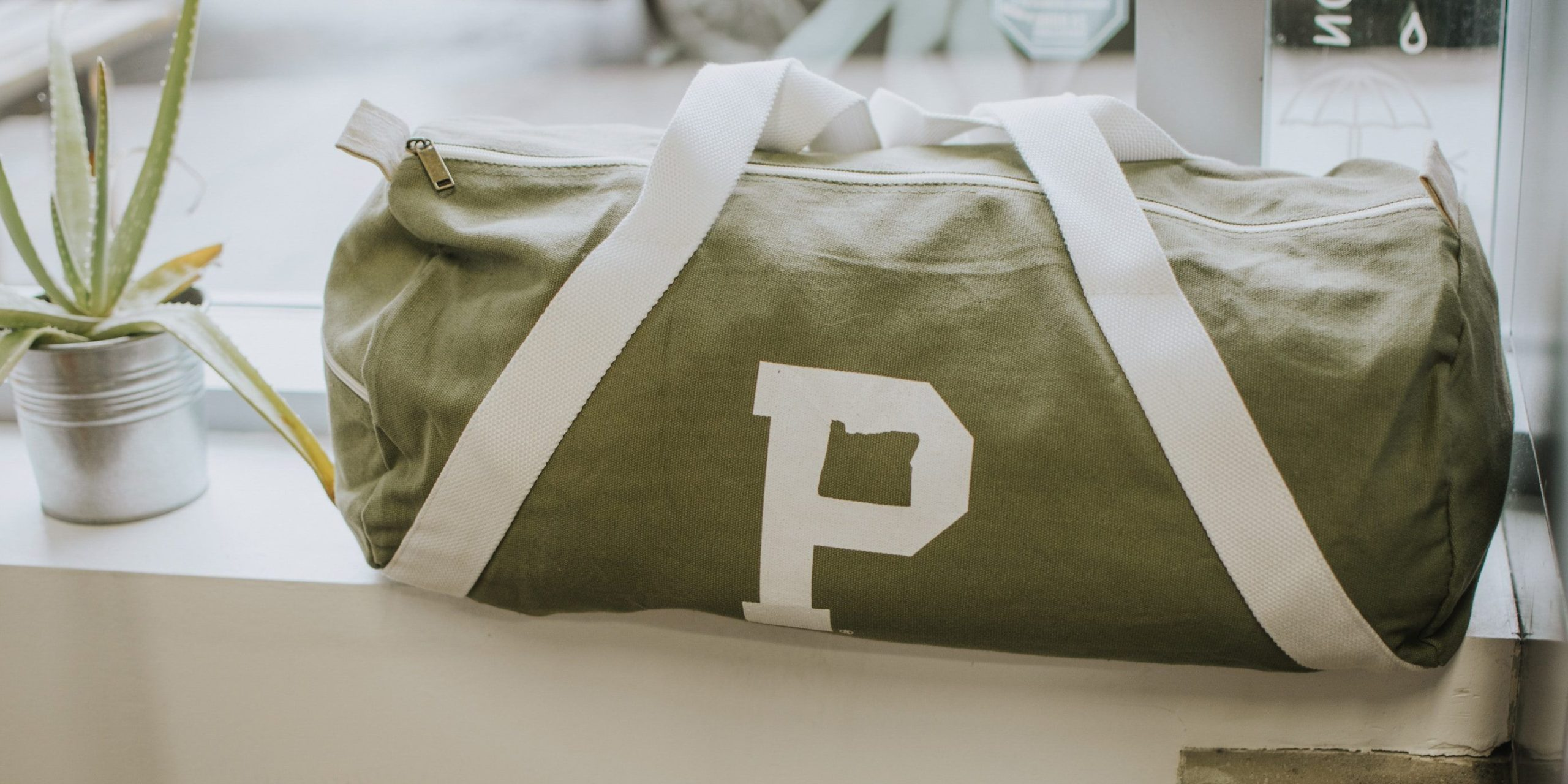 A view of a green canvas duffel bag next to an aloe plant