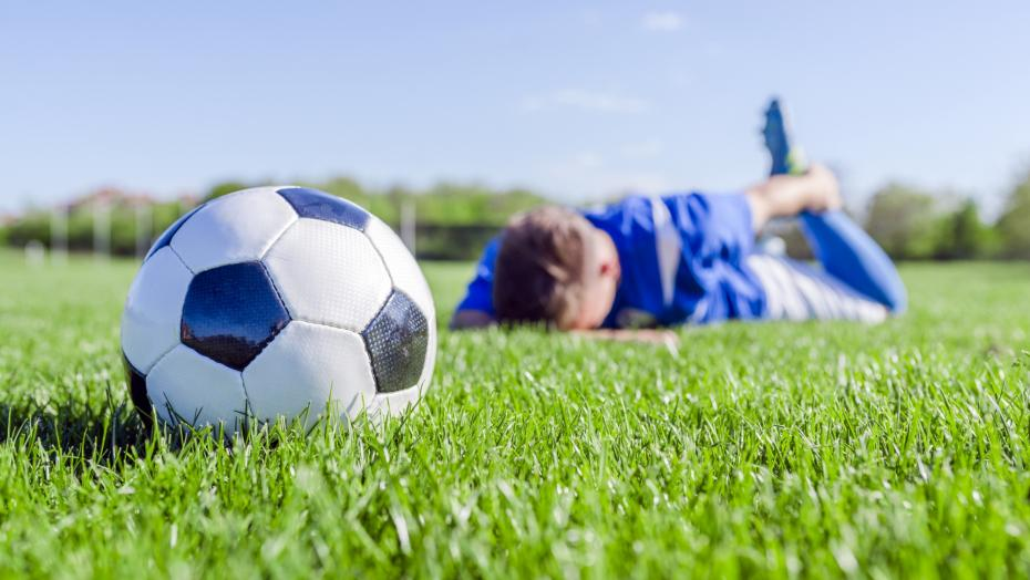 Man lying on stomach in field and holding ankle with soccer ball in foreground