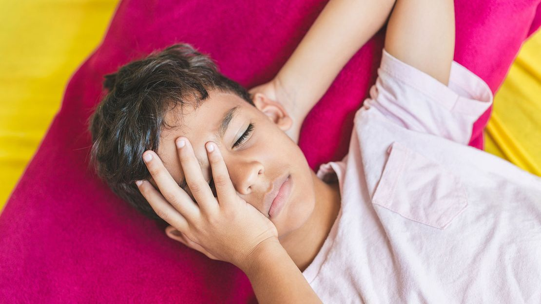 Child with concussion holding head and lying on mat