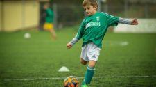 Child kicking orange soccer ball on athletic field
