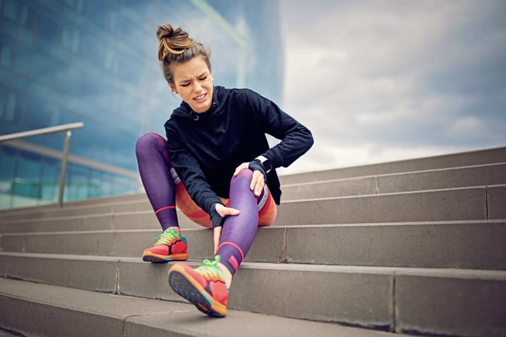 Woman with shin splints grimacing and sitting on staircase