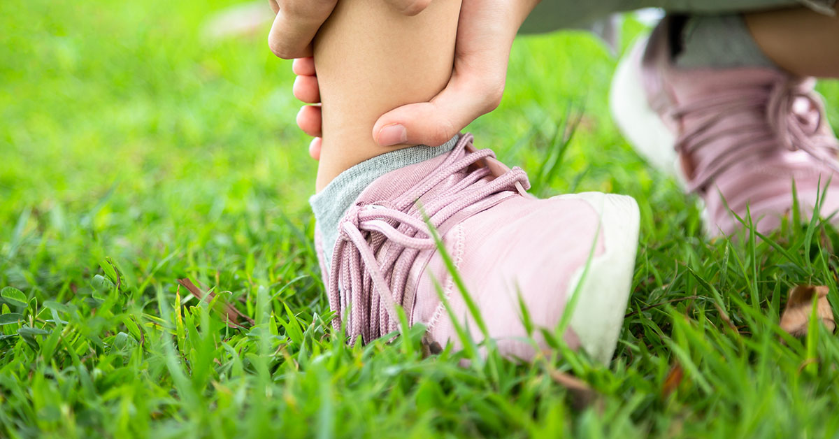 Hand holding sprained ankle of child in grassy field